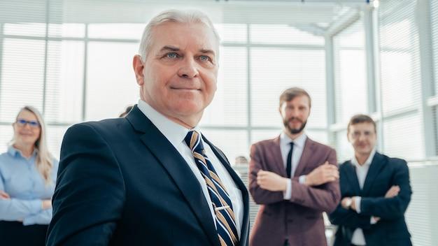Ścieśniać. pewny siebie dojrzały biznesmen stojący w biurze