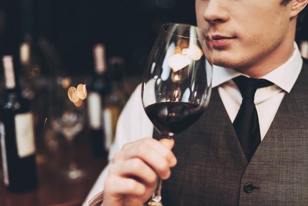 Ścieśniać. pewny siebie przystojny sommelier tasting win.