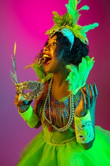 Ścieśniać. piękna młoda kobieta w karnawale, stylowy kostium maskarady z piórami na ścianie gradientu w świetle neonu. koncepcja obchodów świąt, czasu świątecznego, tańca, imprezy, zabawy.