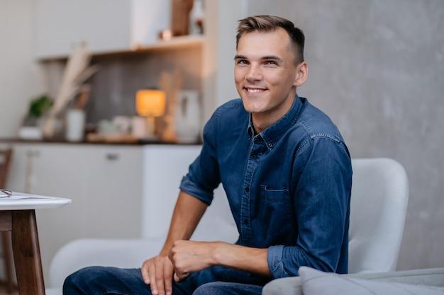 Ścieśniać. portret młodego mężczyzny siedzącego na krześle.