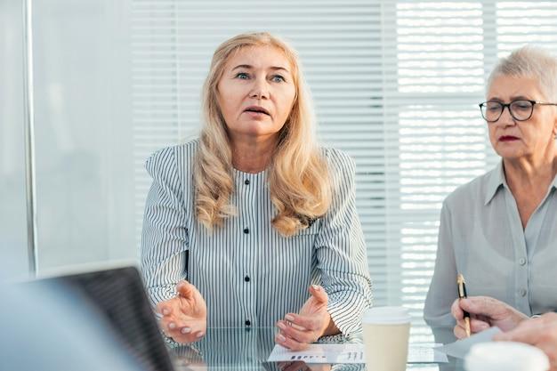 Ścieśniać. poważna biznesowa kobieta wyjaśniająca coś swoim kolegom