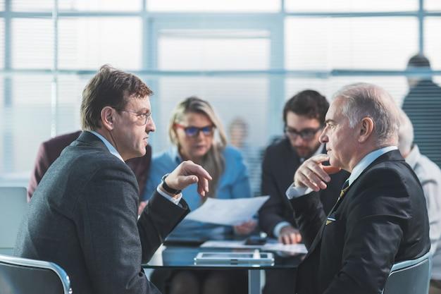 Ścieśniać. poważni ludzie biznesu omawiają problemy na spotkaniu w pracy