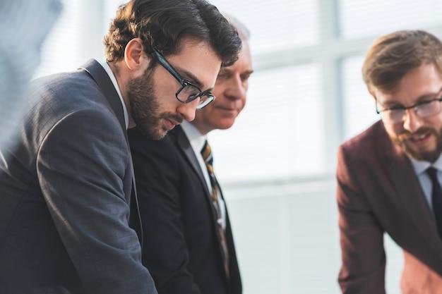 Ścieśniać. poważni współpracownicy stojący w pobliżu pulpitu. pomysł na biznes