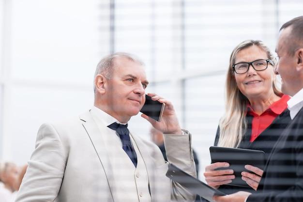 Ścieśniać. poważny biznesmen rozmawia na swoim smartfonie stojącym w biurze. biuro w dni powszednie