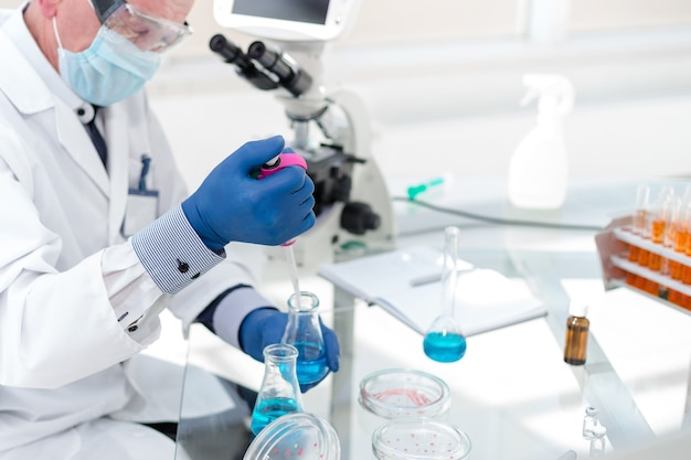 Ścieśniać. pracownicy laboratorium naukowego badający ciecz w kolbie laboratoryjnej.