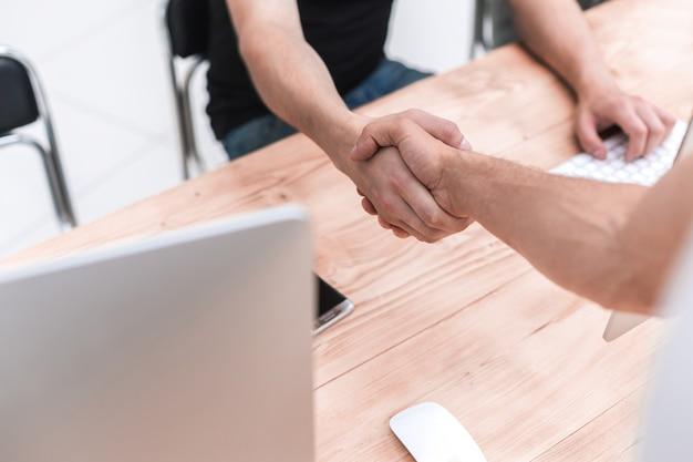 Ścieśniać. pracownicy podają sobie ręce w miejscu pracy. ludzie i technologia