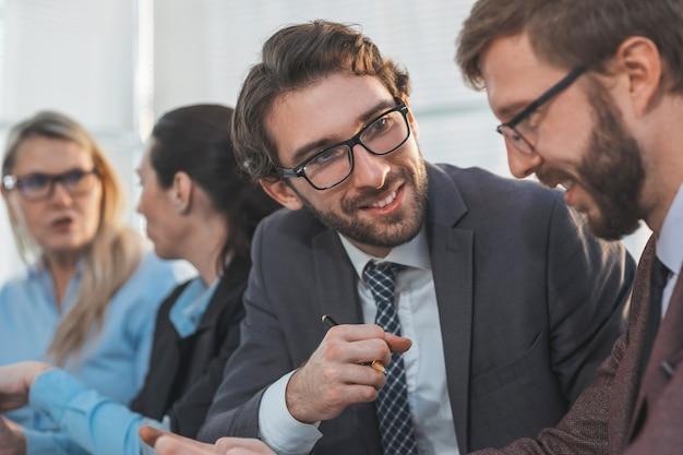 Ścieśniać. pracowników omawiających coś podczas spotkania w biurze.