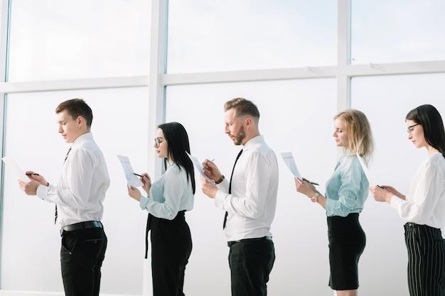Ścieśniać. pracowników z dokumentami biznesowymi stojącymi w kolejce. pomysł na biznes