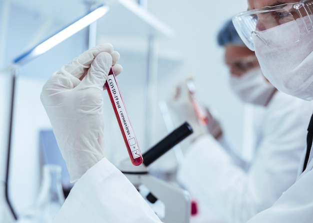 Ścieśniać. probówka z testem w rękach medyka. zdjęcie z miejscem na kopię.