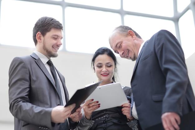 Ścieśniać. przyjaźni koledzy rozmawiający w biurze