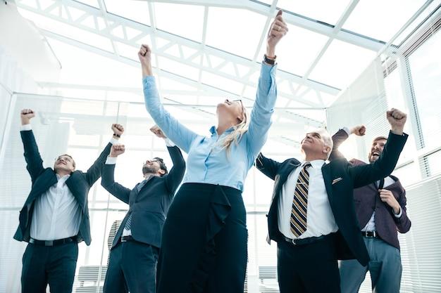 Ścieśniać. radosna kobieta biznesu stojąca przed kolegami