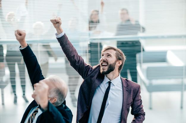 Ścieśniać. radośni koledzy stojący w biurze. zdjęcie z kopią przestrzeni