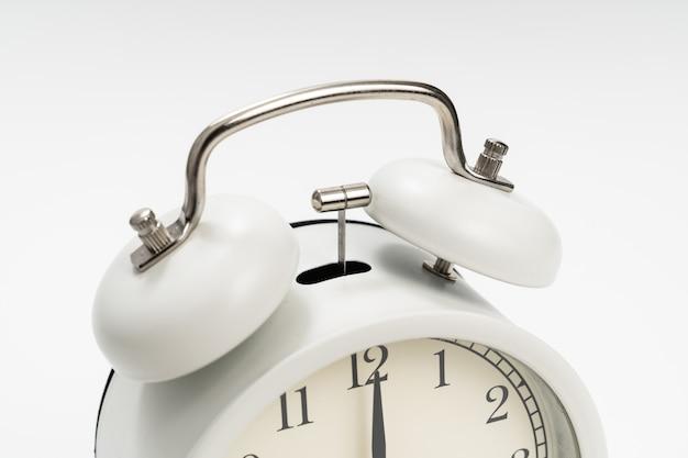 Ścieśniać. retro budzik na białym tle. koncepcja wstępowania wcześnie rano. wyczucie czasu. pierwsza zmiana w szkole lub w pracy.