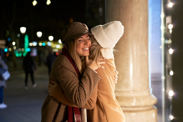 Ścieśniać. spotkanie dwóch młodych kobiet, szczęśliwych i podekscytowanych ponownym spotkaniem, obejmuje się z entuzjazmem