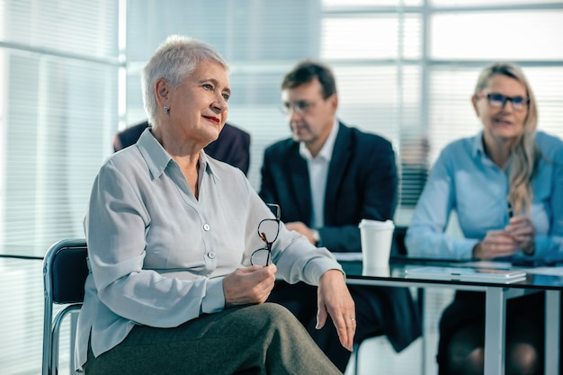 Ścieśniać. starsza bizneswoman siedząca przed biurkiem