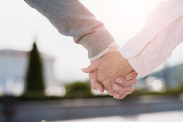 Ścieśniać. starsza para chodzi wokół trzymając się za ręce.