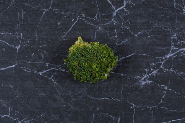 Ścieśniać. świeże, organiczne warzywa. zielone brokuły na czarnym tle.
