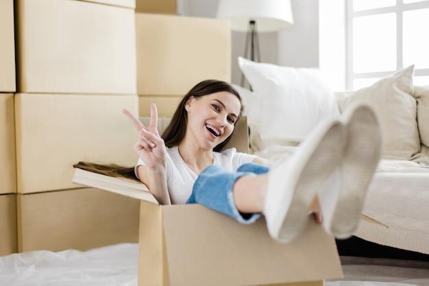 Ścieśniać. szczęśliwa młoda kobieta siedzi w dużym pudełku tekturowym