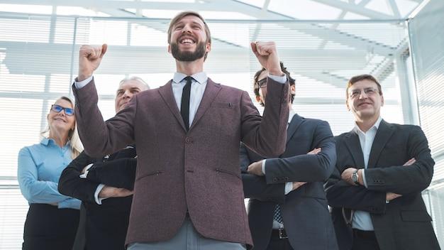 Ścieśniać. szczęśliwy biznesmen stojący przed swoim zespołem. koncepcja sukcesu