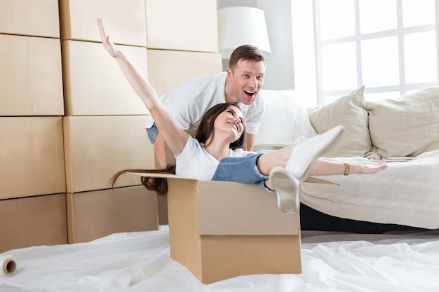 Ścieśniać. szczęśliwy mąż i żona bawią się w swoim nowym mieszkaniu