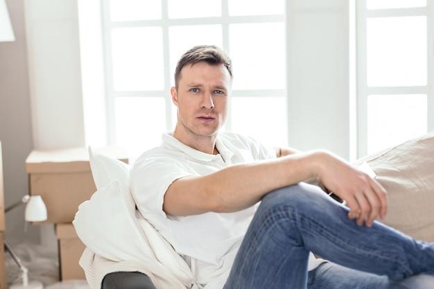 Ścieśniać. szczęśliwy mężczyzna siedzi na kanapie w swoim nowym mieszkaniu