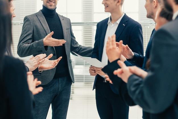 Ścieśniać. szef i zespół biznesowy gratulują koledze