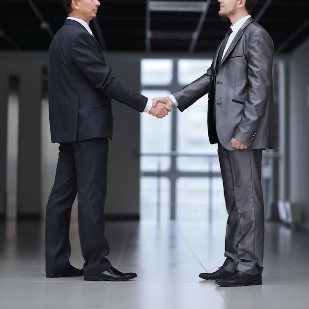 Ścieśniać. uścisk dłoni dwóch ludzi biznesu w biurze. koncepcja partnerstwa