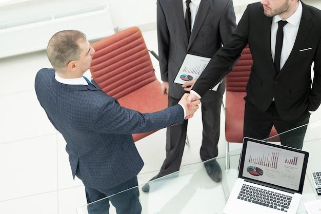Ścieśniać. uścisk dłoni dwóch ludzi biznesu w biurze.