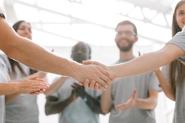 Ścieśniać. uścisk dłoni dwóch studentów na tle zespołu studenckiego. zdjęcie z miejscem na kopię