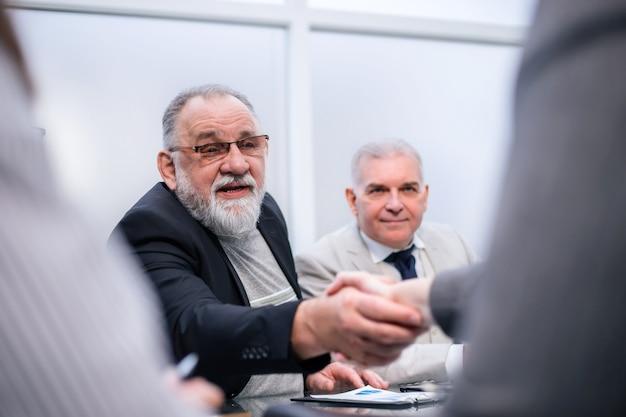 Ścieśniać. uścisk dłoni ludzi biznesu podczas spotkania roboczego. koncepcja współpracy