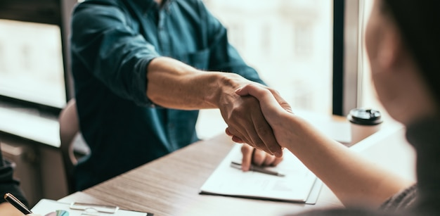 Ścieśniać. uścisk dłoni ludzi biznesu w biurze. koncepcja współpracy.