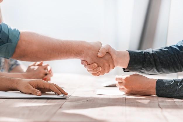 Ścieśniać. uścisk dłoni partnerów biznesowych siedzi przy stole. koncepcja partnerstwa