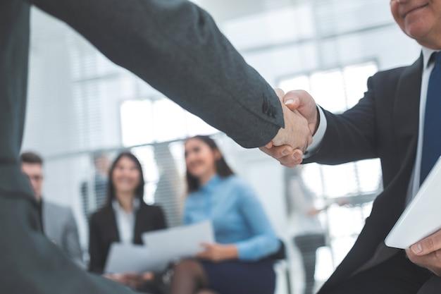 Ścieśniać. uścisk dłoni partnerów biznesowych w tle biura. koncepcja współpracy