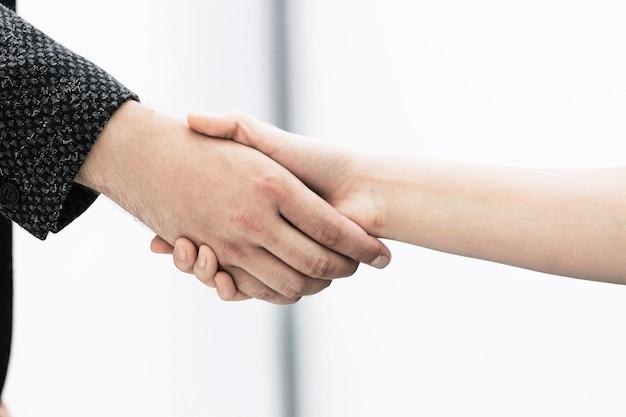 Ścieśniać. uścisk dłoni partnerów finansowych na tle biura. koncepcja współpracy