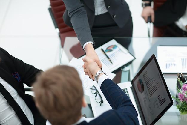 Ścieśniać. uścisk dłoni partnerów handlowych przy stole negocjacyjnym w biurze