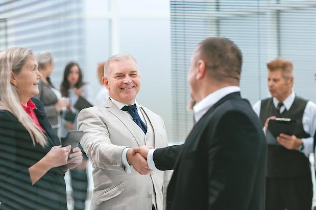 Ścieśniać. uśmiechnięci współpracownicy witają się w holu biura