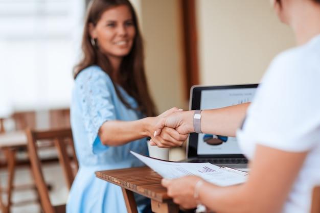 Ścieśniać. uśmiechnięta biznesowa kobieta uścisk dłoni ze swoim partnerem biznesowym. pomysł na biznes.