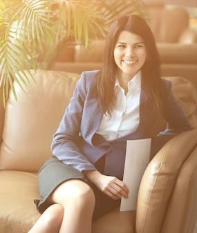Ścieśniać. uśmiechnięta kobieta biznesu siedząca w holu biura
