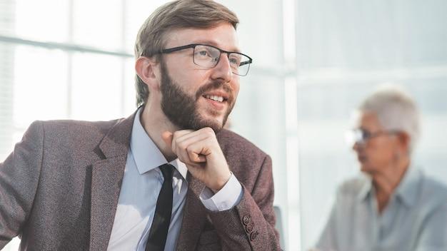 Ścieśniać. uśmiechnięty biznesmen siedzący w biurze ludzie biznesu przy biurku