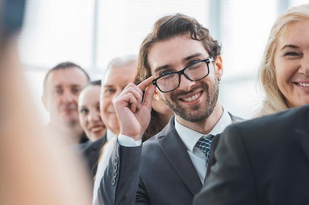 Ścieśniać. uśmiechnięty biznesmen stojący w rzędzie ze swoimi kolegami .zdjęcie z kopią przestrzeni