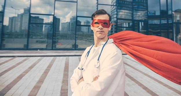 Ścieśniać. uśmiechnięty lekarz superbohater czekamy. zdjęcie z kopią miejsca.
