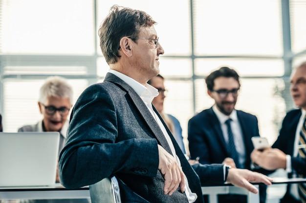 Ścieśniać. uśmiechnięty młody biznesmen siedzący przy biurku