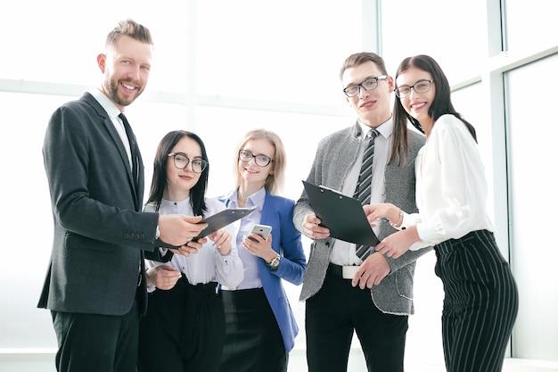 Ścieśniać. uśmiechnięty zespół biznesowy z dokumentami biznesowymi. koncepcja sukcesu