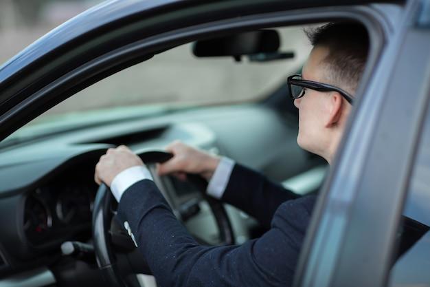 Ścieśniać. wesoły biznesmen pokazujący kluczyki do swojego nowego samochodu