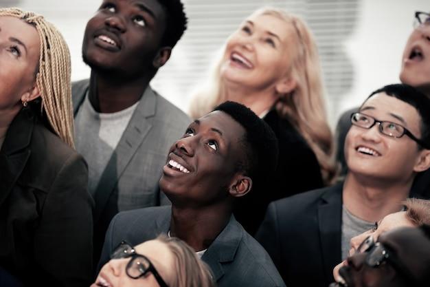 Ścieśniać. wielonarodowa grupa młodych ludzi biznesu, patrząc w górę