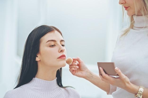 Ścieśniać. wizażystka robi profesjonalny makijaż młodej kobiety