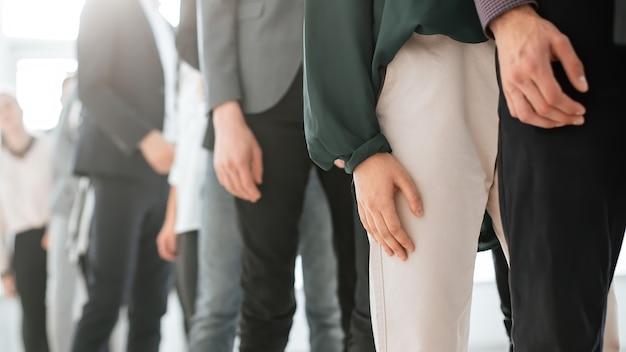 Ścieśniać. wizerunek młodych ludzi biznesu stojących w długiej kolejce