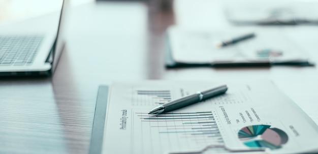 Ścieśniać. wykres finansowy i długopis na pulpicie. zaplecze biznesowe.