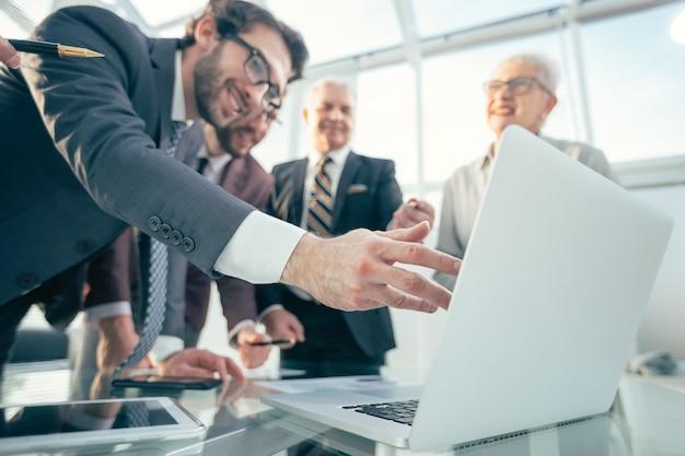 Ścieśniać. zadowolonych pracowników patrząc na ekran laptopa. pomysł na biznes