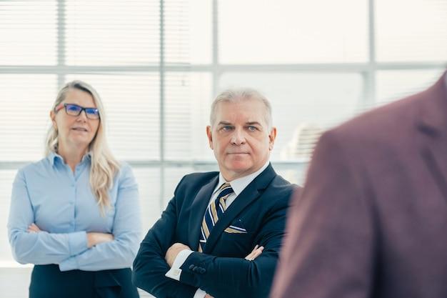 Ścieśniać. zamyśleni, poważni pracownicy stojący w biurze. ludzie biznesu